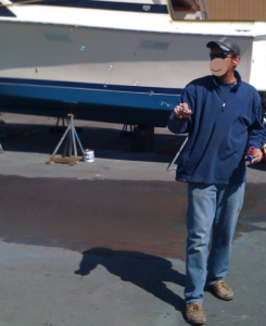 In front of a boat propped up on blacktop, a man holds a bubble wand with bubbles streaming away, lit up by sunlight.