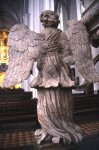 Rear view of sturdy stone angel inside a lovel stone church