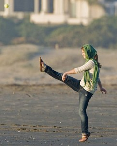 girl on a flat beach kicking a ball high