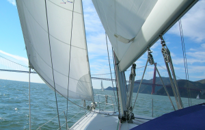 view forward from deck of sailboat. Mainsail on right, jib on left, Marin headlands and Golden Gate visible between.