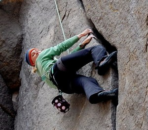 woman climbing up a crack in a steep rockface, hands pulling one way and feet pushing the other