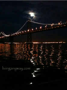 full moon clearing clouds over illuminated Bay Bridge, all reflected in the black water