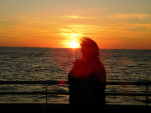 woman looking at sunset over water, dog nose poking out of jacket.