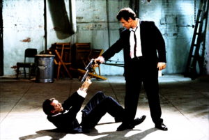 two tense men, one standing, one curled on his back, pointing guns at each other