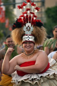 Big grinning woman in spectacular Hawaiian ceremonial dress dancing with her arms